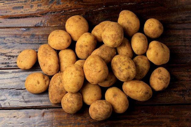 Kupie świeże i surowe ziemniaki zebrane z plantacji i umieszczone rustykalny drewniany stół