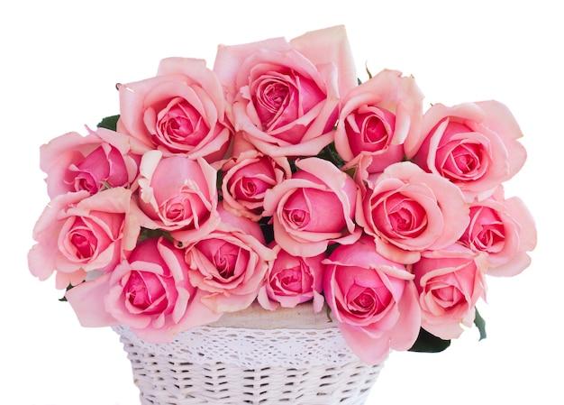 Kupie świeże różowe kwitnące róże w koszu na białym tle