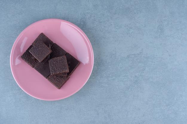 Kupie świeże wafle czekoladowe na różowym talerzu.