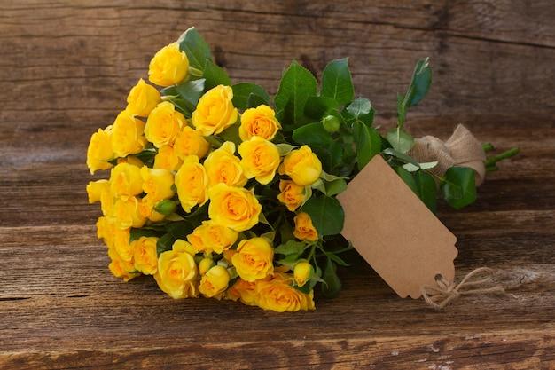 Kupie świeże żółte róże z pustą notatką papieru na drewnianym