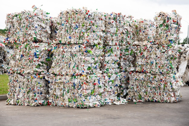 Kupie tłoczone białe plastikowe butelki w zakładzie zbiórki śmieci
