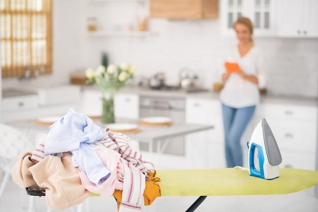 Kupie ubrania i żelazko na desce do prasowania i kobieta z tabletem w tylnej części kuchni