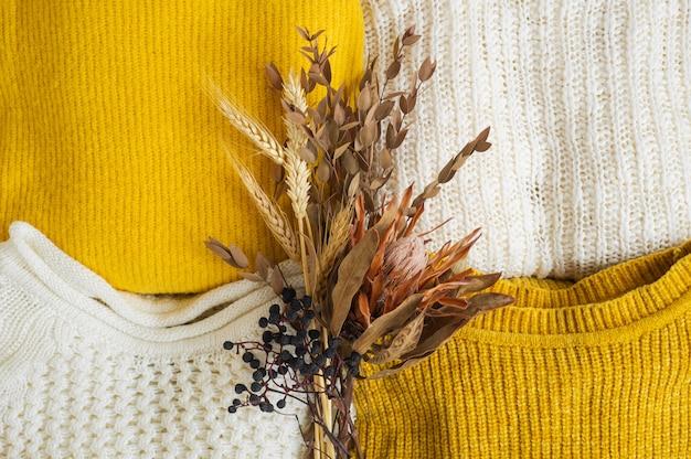 Kupie ubrania z dzianiny z bukietem suszonych kwiatów