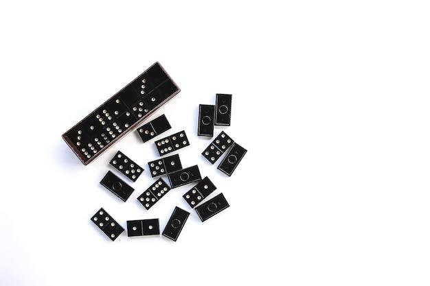 Kupie vintage czarne płytki domino i domino w polu na jasnym tle.
