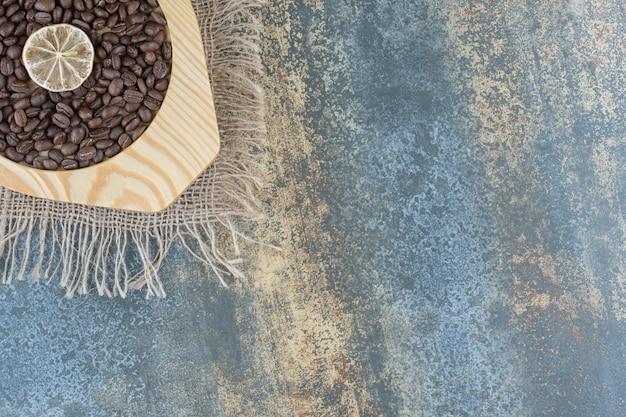 Kupie ziarna kawy i plasterek cytryny na drewnianym talerzu.