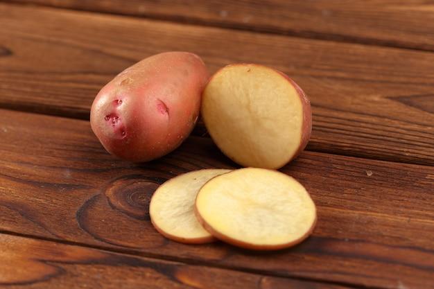 Kupie ziemniaki leżące na deskach