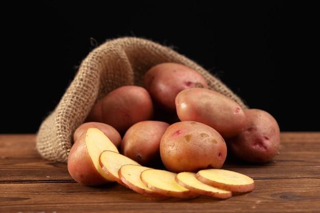Kupie ziemniaki leżące na drewnianych deskach