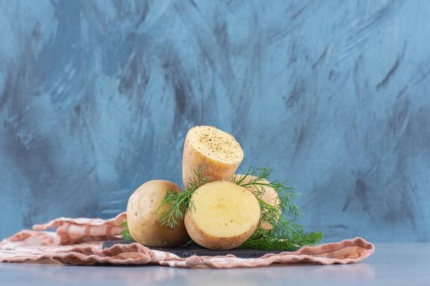Kupie ziemniaki leżące na szarym tle.