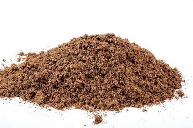 Kupie żyznej gleby na białym tle. nieostrość.