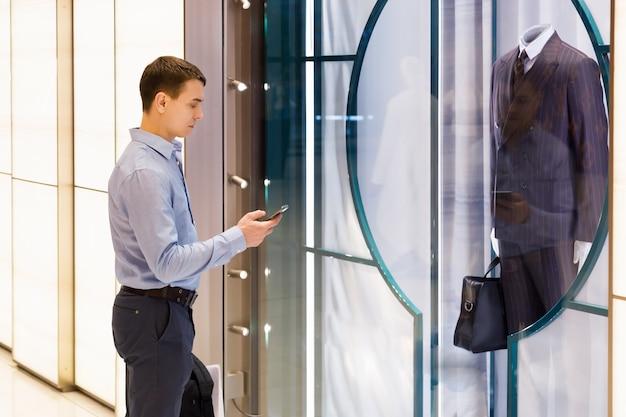 Kupiec kaukaski mężczyzna z telefonem stał obok luksusowego męskiego garnituru w oknie supermarketu.
