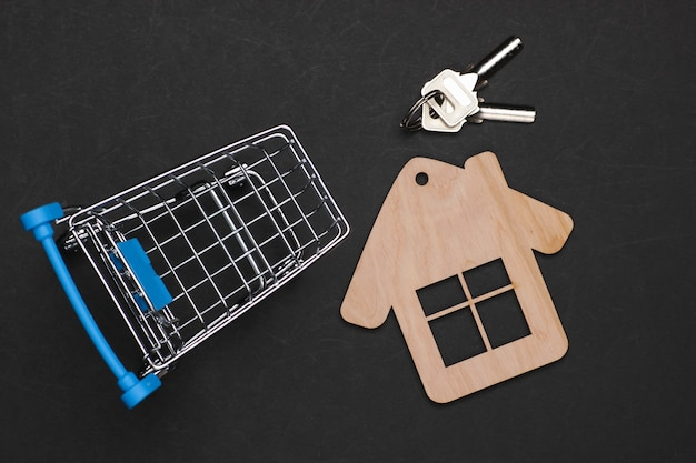 Kupno domu, miniaturowej martwej natury. wózek na zakupy z postacią domu na czarnym tle.