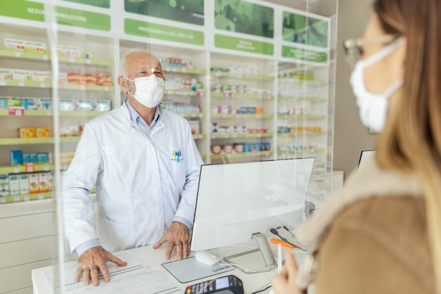 Kupno i sprzedaż leków na receptę oraz porady farmaceuty. uśmiechnięty starszy farmaceuta płci męskiej stojący za ladą i sprzedający leki dorosłej dziewczynie w masce ochronnej