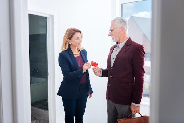 Kupno mieszkania. doświadczona piękna agentka nieruchomości bierze kartę swojego klienta kupującego nowy luksusowy apartament w centrum miasta