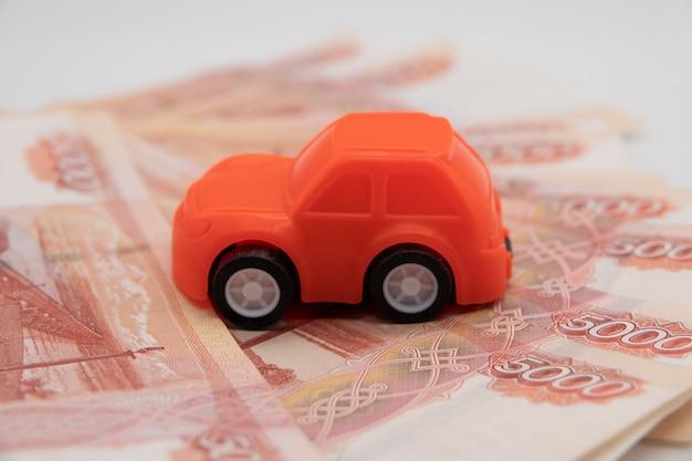 Kupno samochodu w rublach autko na tle banknotów.