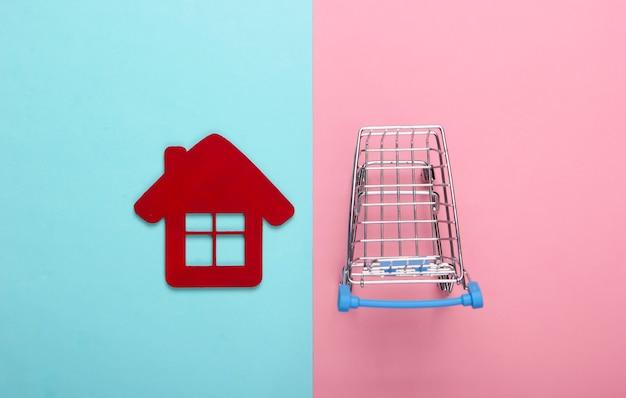 Kupowanie koncepcji domu. wózek sklepowy z postacią domu na różowym niebieskim tle. widok z góry