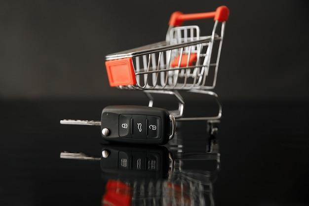 Kupowanie nowego car.car zakupy, kluczyki do samochodu obok koszyka.podobne zdjęcia