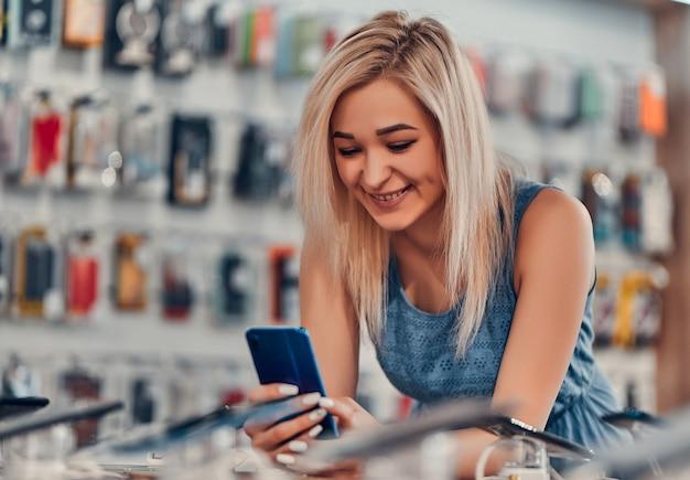 Kupowanie nowego smartfona w sklepie technologicznym. szukasz nowego, spokojnego gadżetu technologicznego. piękna kobieta w zakupach.
