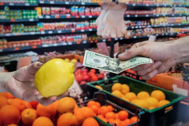 Kupowanie owoców w supermarkecie. kupujący daje gotówkę za zakup. dolar w ręku