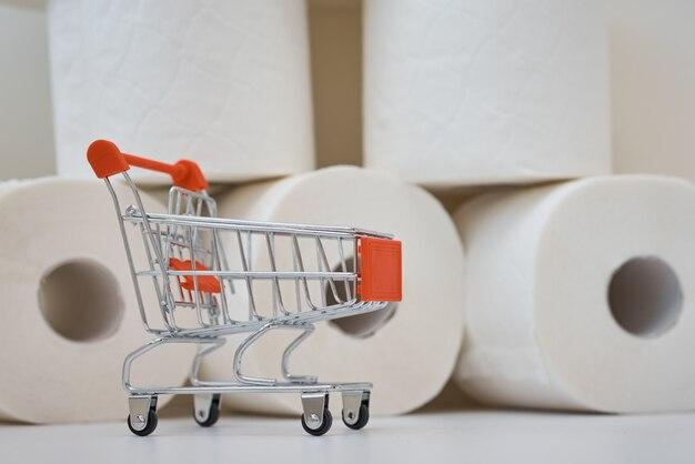 Kupowanie paniki na temat koncepcji koronawirusa covid-19. wózek na zakupy i rolki papieru toaletowego