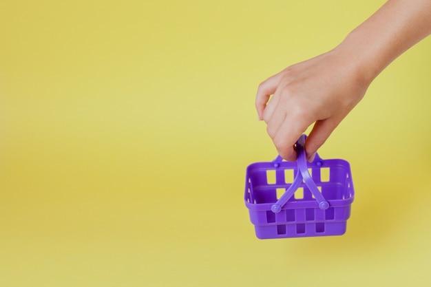 Kupowanie rzeczy w koncepcji sklepów na rynku. kobieta ręka trzyma mały mały koszyk na zakupy wózek na trend żółtym tle.
