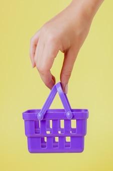 Kupowanie rzeczy w koncepcji sklepów na rynku. kobieta ręka trzyma mały mały koszyk na zakupy wózek nad trend żółtą ścianą.