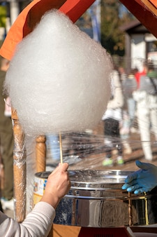 Kupowanie waty cukrowej na ulicy robienie cukierków uliczne słodycze na patyku w dłoni