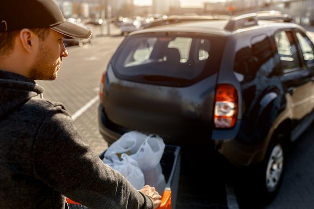 Kupowanie żywności w supermarkecie. zakupy młody mężczyzna kupuje jedzenie przez tydzień w dużym centrum handlowym na wsi. składa torby warzyw, owoców, mięsa i produktów mlecznych na parkingu