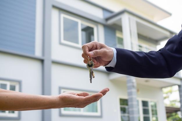 Kupujący biorą klucze do domu od sprzedawców. sprzedaj swój dom, wynajmij dom i kupuj pomysły.