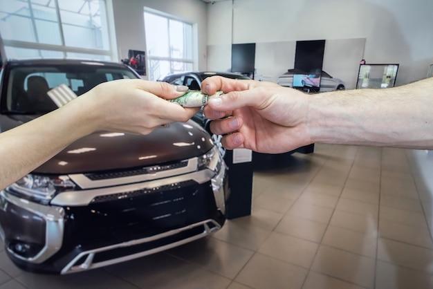 Kupujący daje pieniądze na zakup lub wynajem nowego samochodu. koncepcja udanej transakcji.