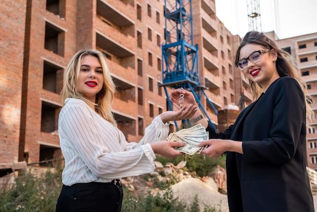 Kupujący daje sprzedającemu dolary na tle domu. kupno lub wynajem nowego domu