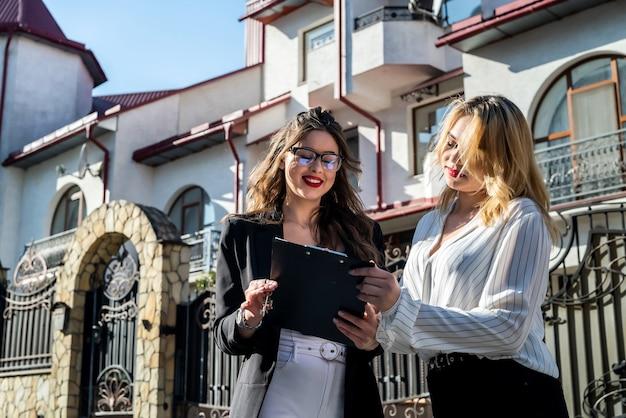 Kupujący i pośrednik podpisują umowę kupna mieszkania w wielopiętrowym budynku w tle