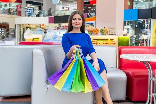 Kupujący kobieta pokazuje jej kolorowe torby w centrum handlowym