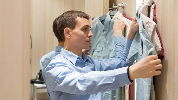 Kupujący mężczyzna z kilkoma rzeczami wybiera ubrania w szatni.