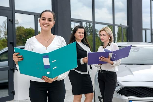 Kupujący patrząc na umowę kupna samochodu w pobliżu nowego samochodu