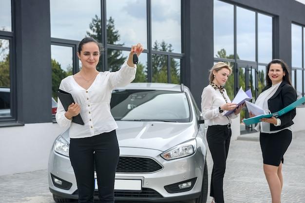 Kupujący patrzący na umowę kupna samochodu w pobliżu nowego samochodu. mają w rękach duże teczki z dokumentami
