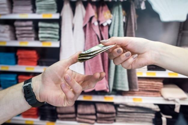Kupujący płaci kasjerowi za swoje towary