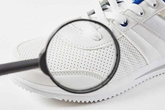 Kupujący szuka defektów i szczegółów makro w butach z lupą stylowe trampki