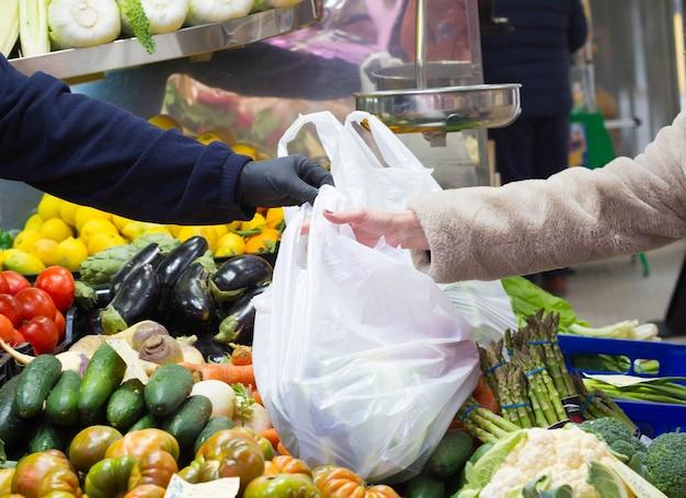 Kupujący w rękawiczkach na tle warzyw w supermarkecie koncepcja ochrony przed koronawirusem