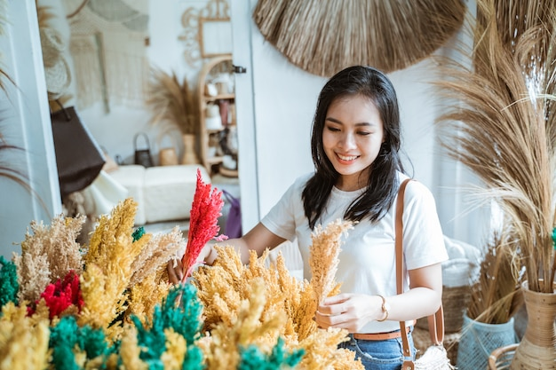 Kupujący wybiera i trzyma sztuczne rośliny wykonane z naturalnych materiałów spośród przedmiotów rękodzieła w galerii rękodzieła