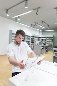 Kupujący wybiera komputer typu tablet w sklepie z technologią lekką