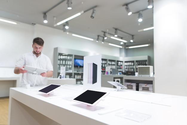 Kupujący wybiera tablet w sklepie elektronicznym.