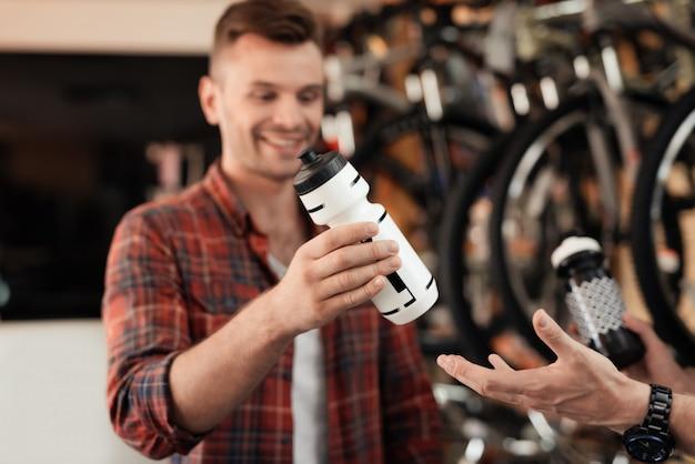 Kupujący wybrał w sklepie butelkę z białą wodą.