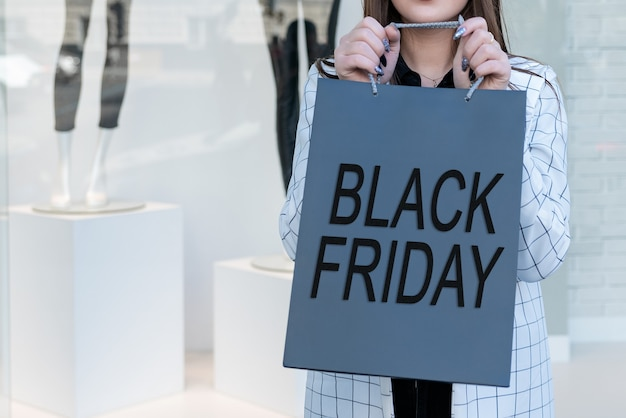 Kupujący z papierową torbą na czarny piątek w centrum handlowym
