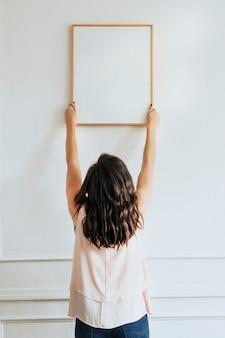 Kurator zawiesza pustą ramkę na ścianie