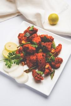 Kurczak 65 pikantna przystawka do baru lub szybka przekąska z indii w misce lub talerzu na białym tle
