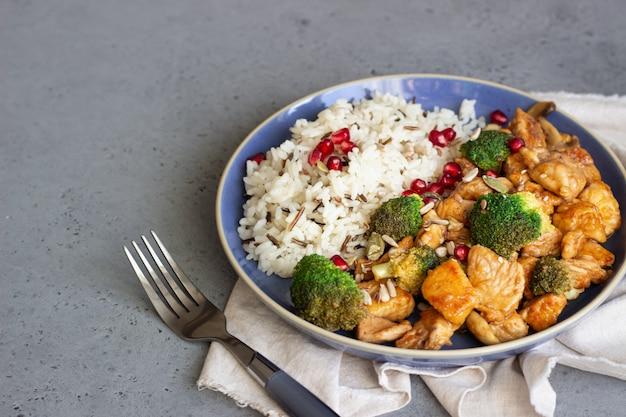 Kurczak curry z ryżem, grzybami i brokułami ozdobiony pestkami granatu