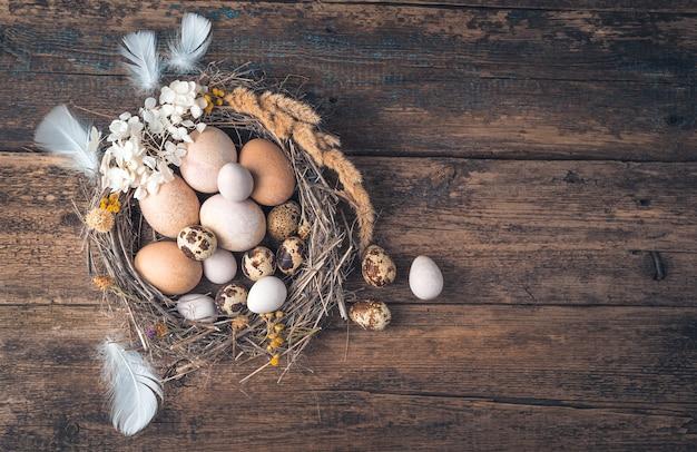 Kurczak i jaja przepiórcze malowane naturalnymi barwnikami w gnieździe na drewnianym tle.