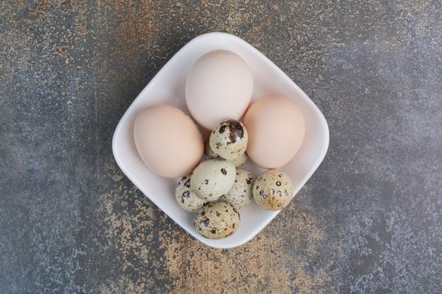 Kurczak i jaja przepiórcze na białej misce