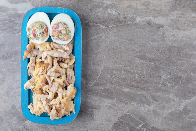 Kurczak i jajka na twardo z sałatką na niebieskim talerzu.