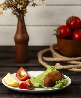 Kurczak ievºiev plasterek cytryny i pomidora na drewnianym stole